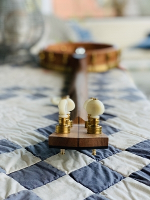Brass tuners with vintage-cream knobs set on book-matched cherry neck with walnut center stripe.