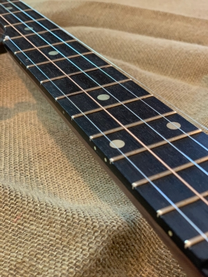 Solid brass fret markers inlayed on ebony fingerboard with brass inlay side dots